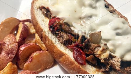 Steak hoagie sandwich with mushrooms peppers and cheese with potatoes