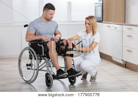 Young Female Physiotherapist Fixing Knee Braces On Man's Leg In A Clinic