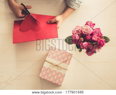 Top view of little girl cutting a red paper heart while making a present cropped