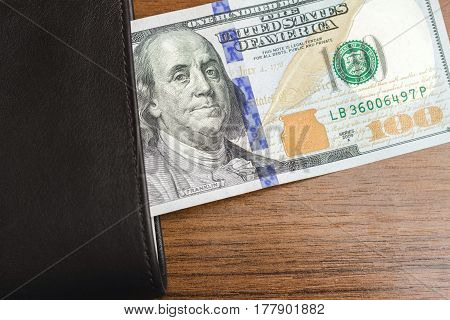 Wallet with hundred dollar banknotes on wooden background money and finance concept