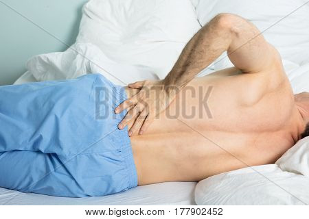 Close-up Of A Man Lying On Bed Suffering From A Back Pain At Home