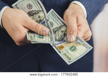 Close-up of male hands hold hundred dollars banknotes business and finance concept