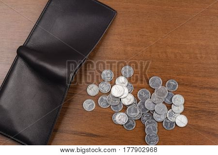 Wallet with ukrainian coins kopiyka on wooden background top view