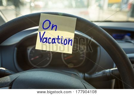 Close-up Of A Vacation Concept Written On Steering Wheel Of A Car