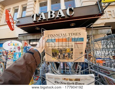 PARIS FRANCE - MAR 23 2017: Man purchases a Financial Times newspaper from press kiosk newsstand featuring headlines following the terrorist incident in London at the Westminster Bridge
