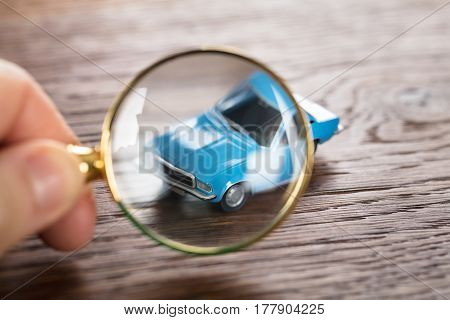 Person Scrutinizing A Car Model Using Magnifying Glass On Wooden Desk