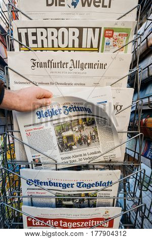 PARIS FRANCE - MAR 23 2017: Point of view of man purchasing German Kehler Zeitung newspaper from press kiosk newsstand featuring headlines following the terrorist incident in London at the Westminster Bridge