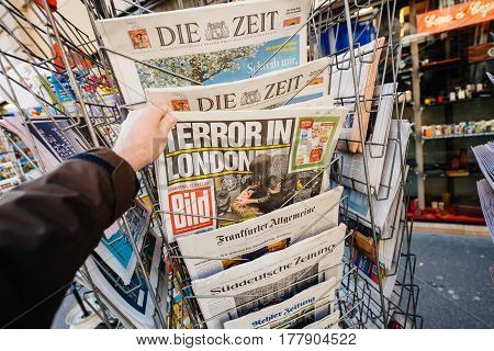 PARIS FRANCE - MAR 23 2017: POV Man purchases newspaper German Bild from press kiosk newsstand featuring Terror in London headlines following the terrorist incident in London at the Westminster Bridge