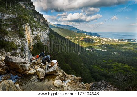Hickers lying on a ledge in mountains, looking down the waterfall. Three hikers lay on the edge of rock staring down the steep watching beautiful landscape