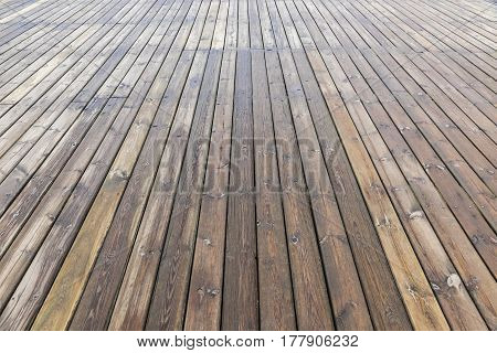 Old wooden brown background texture with perspective. Wooden planks that make up a large pier