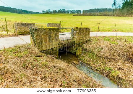 Old Small Bridge With A Rural Path And Green Meadow Behind And A Running Stream - European Countrysi