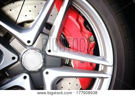 The closeup of spoke wheels of a sports car with the brake discs.