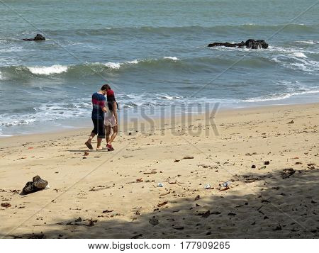 Young happy couple walking on beach holding hands