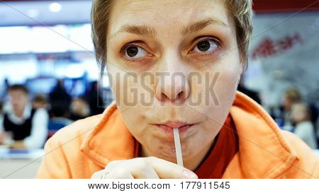 Young woman drinks cola through drinking straw in fast food cafe restaurant