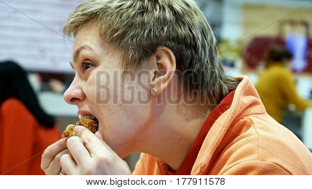 Young woman eats fast food chicken nuggets wings in cafe restaurant