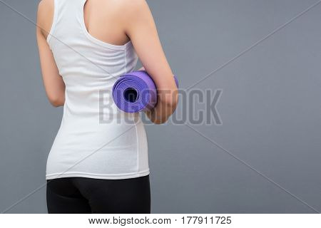 Young asian woman holding her yoga mat at yoga healthy sport gym. Yoga and meditation have good benefits for health. Photo concept for Yoga Sport and Healthy lifestyle.