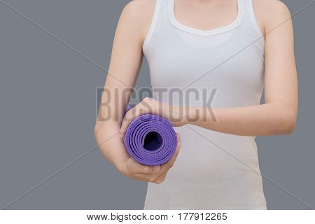 Young asian woman holding her yoga mat at yoga healthy sport gym. Yoga and meditation have good benefits for health. Photo concept for Yoga Sport and Healthy lifestyle