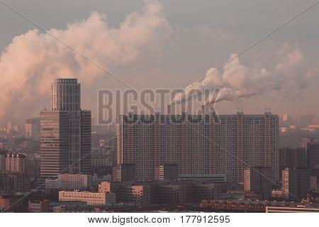 View from top of morning metropolitan city: office business skyscraper and huge residential building and districts with two fuming chimneys behind multiple facades windows hazy horizon Moscow