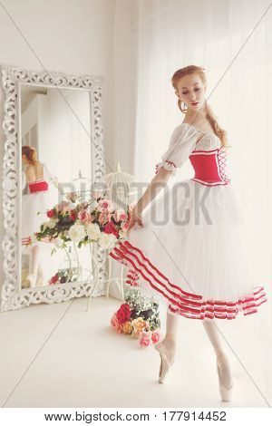 Nice ballerina in a stage costume stands on her fingers. Retro dress.