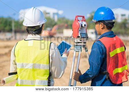 Construction Engineer Hodling Construction Drawing And Smart Tablet With Foreman Worker Checking Con