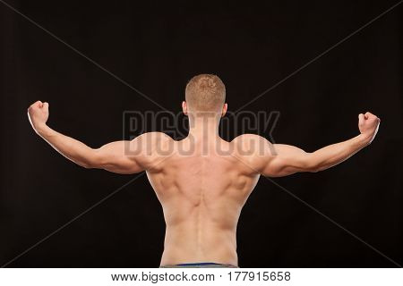 Athletic handsome sportsman fitness-model showing his muscular back. isolated on black background with copyspace.
