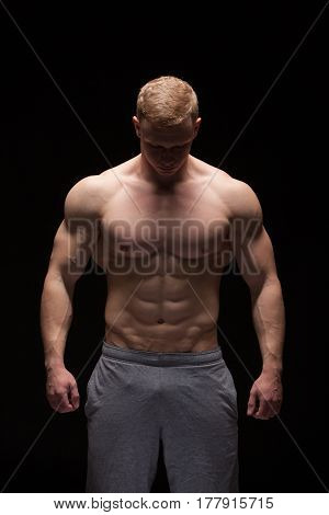 Athletic handsome man fitness-model is showing six pack abs. isolated on black background with copyspace.