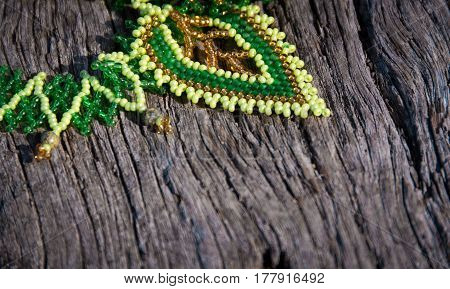 green bead-work lace on a wooden background. Soft selective focus and shallow depth of field.