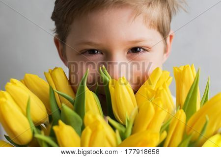 Portrait Smiling Cute Boy with Yellow Bouquet Tulips for Mammy Spring Flowers Concept Mother's Day Valentines Gift for Woman