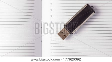 Flash drive on an open diary black compact small device for storing information white pages with black lines
