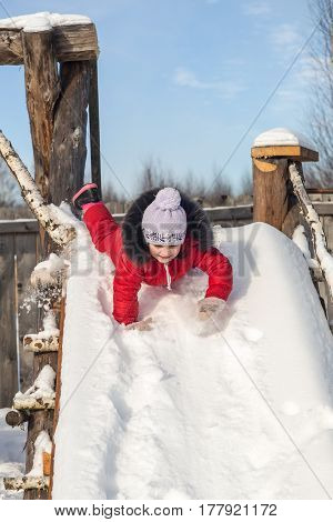 Little girl is riding on a hill in winter
