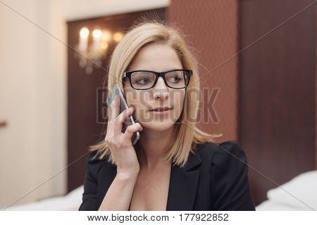 Good business talk. Cheerful young beautiful woman in glasses talking on mobile phone