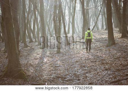 Beautiful young woman wearing sport clothes, standing in the misty forest.