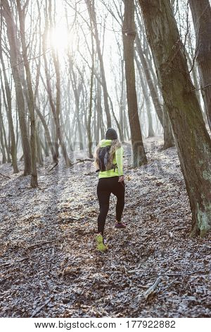 Runner is running through misty morning autumn forest. Sporty young female runner in forest. Running woman. Female runner during outdoor workout in nature. Fitness model outdoors. Weight Loss.