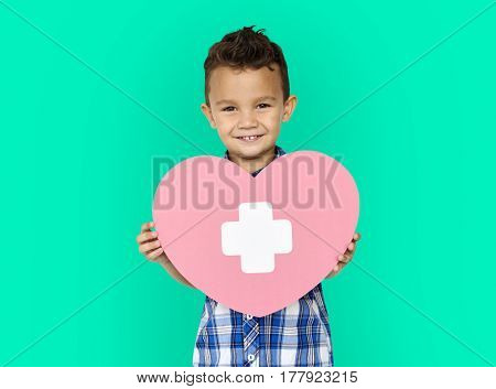 Boy holding healthcare heart paper craft on green background