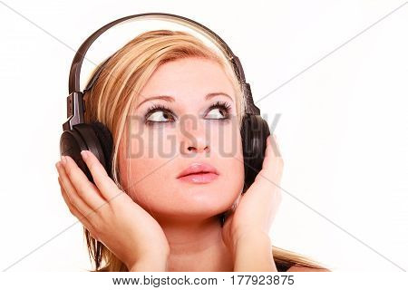 Portrait musicaly passion concept. Studio shot blonde young woman listening to music on big headphones looking up and thinking isolated