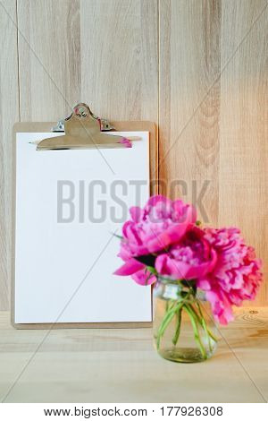 blank clipboard and pink peony bouquet in wooden interior