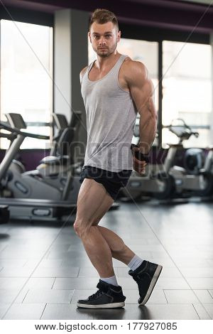 Muscular Man Flexing Muscles In Gym In Undershirt