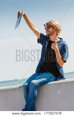 Contacts technology self-esteem concept. Young blonde man on vacations using his tablet to take cool selfie shot showing thumb up gesture