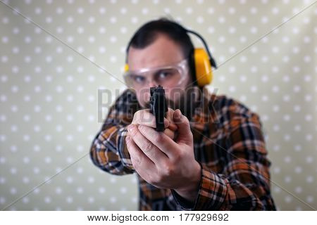 bearded man with put on protective goggles and ear training in pistol shooting
