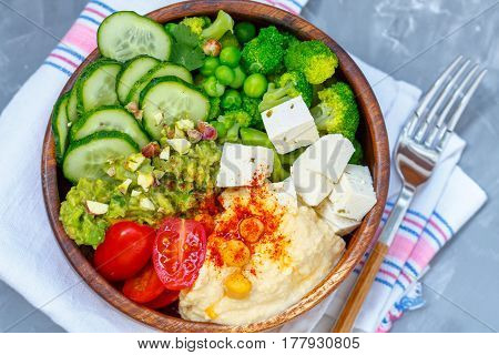 Bowl of bright healthy vegan lunch: vegetable salad with tofu hummus and guacamole. Buddha rainbow wooden bowl vegan concept.