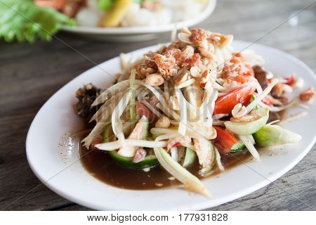 Som-Tum, papaya salad is the most popular dish of Thai food on white plate