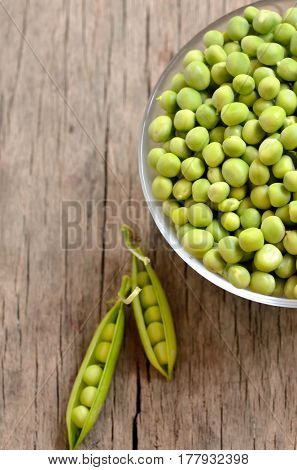 Green peas in a bowl on a wooden background