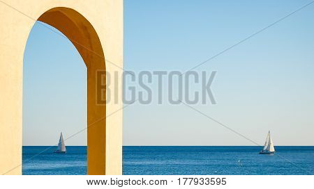 view of blue sea and sky in varigotti from an arch