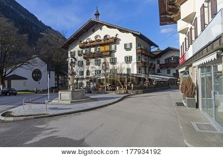 MAYRHOFEN AUSTRIA - MARCH 5 2017: Decorated in the traditional Tyrolean style facade of the hotel. Mayrhofen - ski resort town in Austrian Alps. March a sunny day.