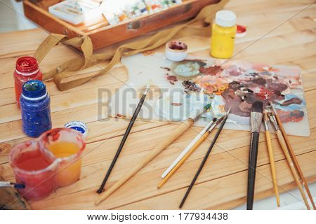 The Artist's Palette. Colored Oil Paints Over A Pallete On A Table.