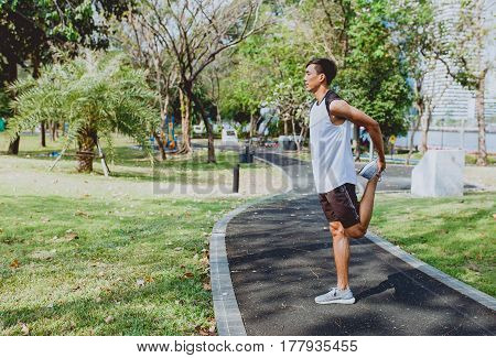 Young man stretching bodies warming up for jogging.