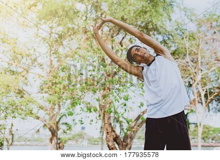 Young man stretching bodies warming up for jogging in public park.
