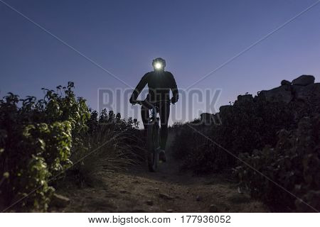Cyclist descends the hill at night lit by lantern