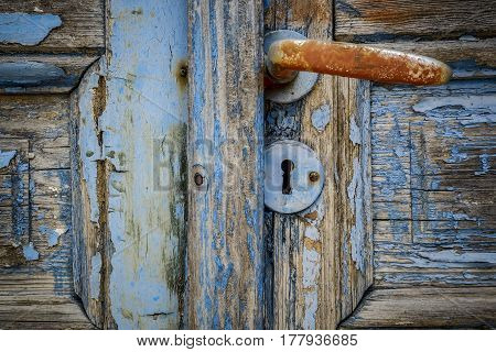 keyhole underneath a brown handle on a weathered dirty old door
