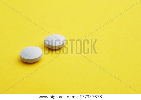 Pills over a yellow background. Medicament treatment. Health care photo